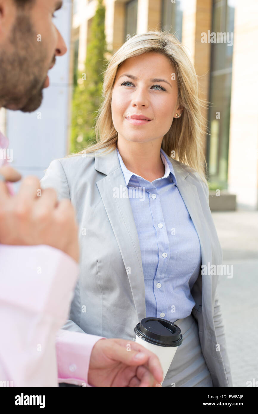 Businesswoman looking at male colleague outdoors - Stock Image