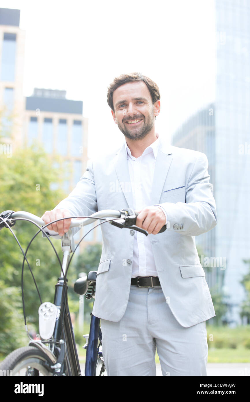 Portrait of happy businessman holding bicycle outdoors - Stock Image
