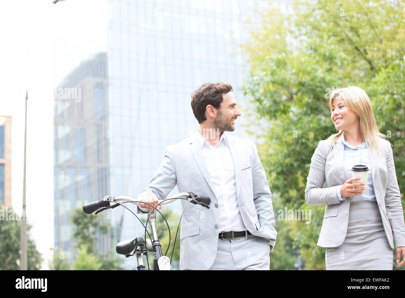 Businesspeople with bicycle and disposable cup conversing while walking outdoors - Stock Image