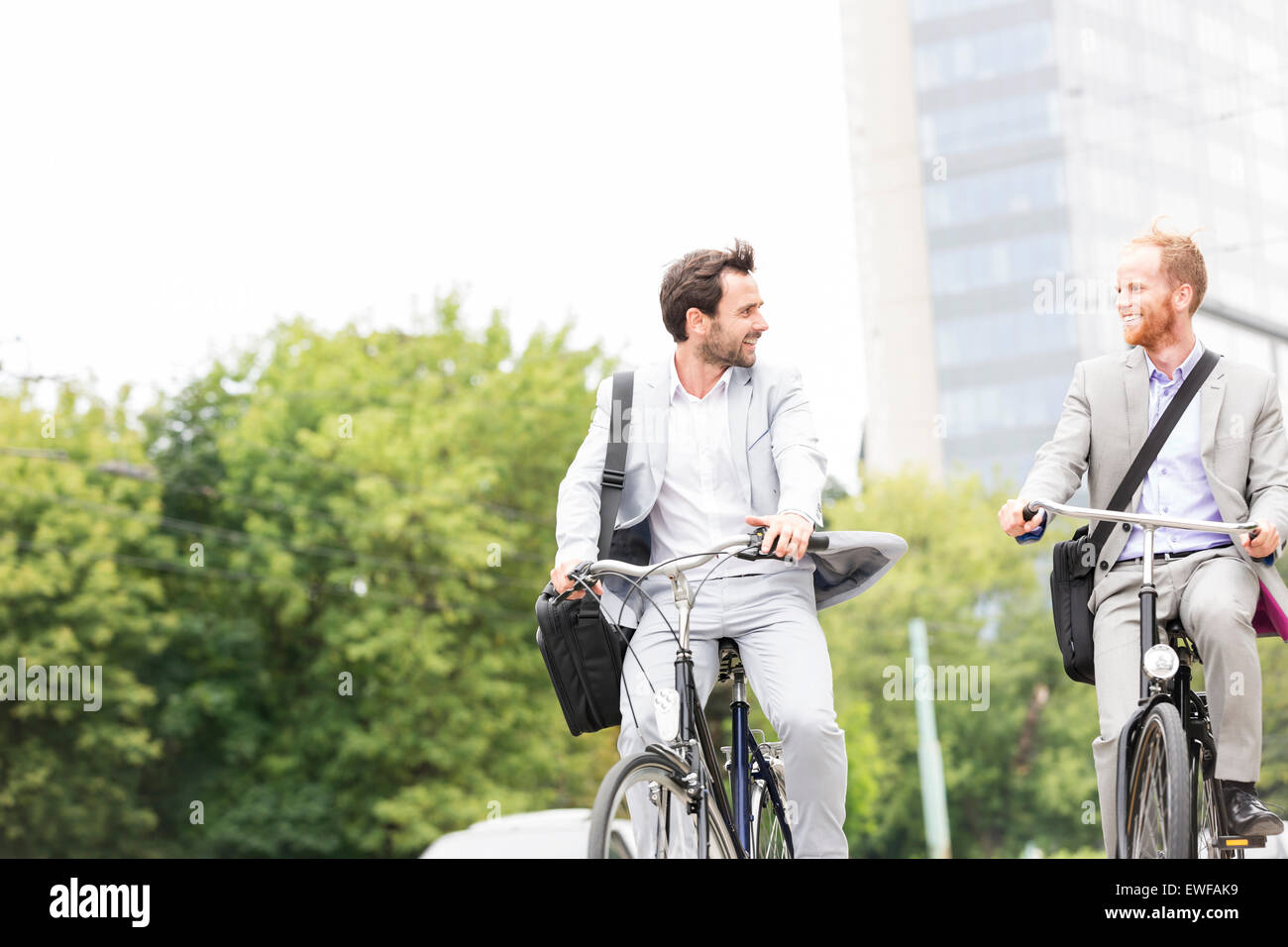 Businessmen talking while riding bicycles outdoors - Stock Image