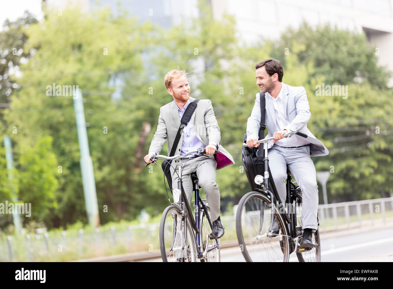 Businessmen talking while cycling outdoors - Stock Image