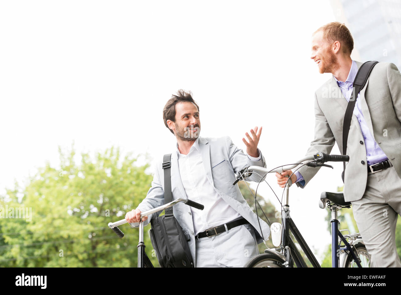 Businessmen talking while walking with bicycles outdoors - Stock Image