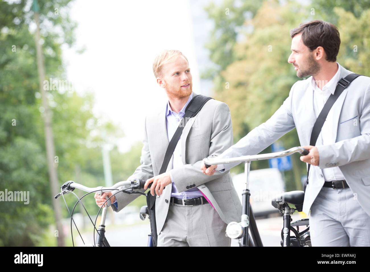 Businessmen looking at each other while holding bicycles outdoors - Stock Image