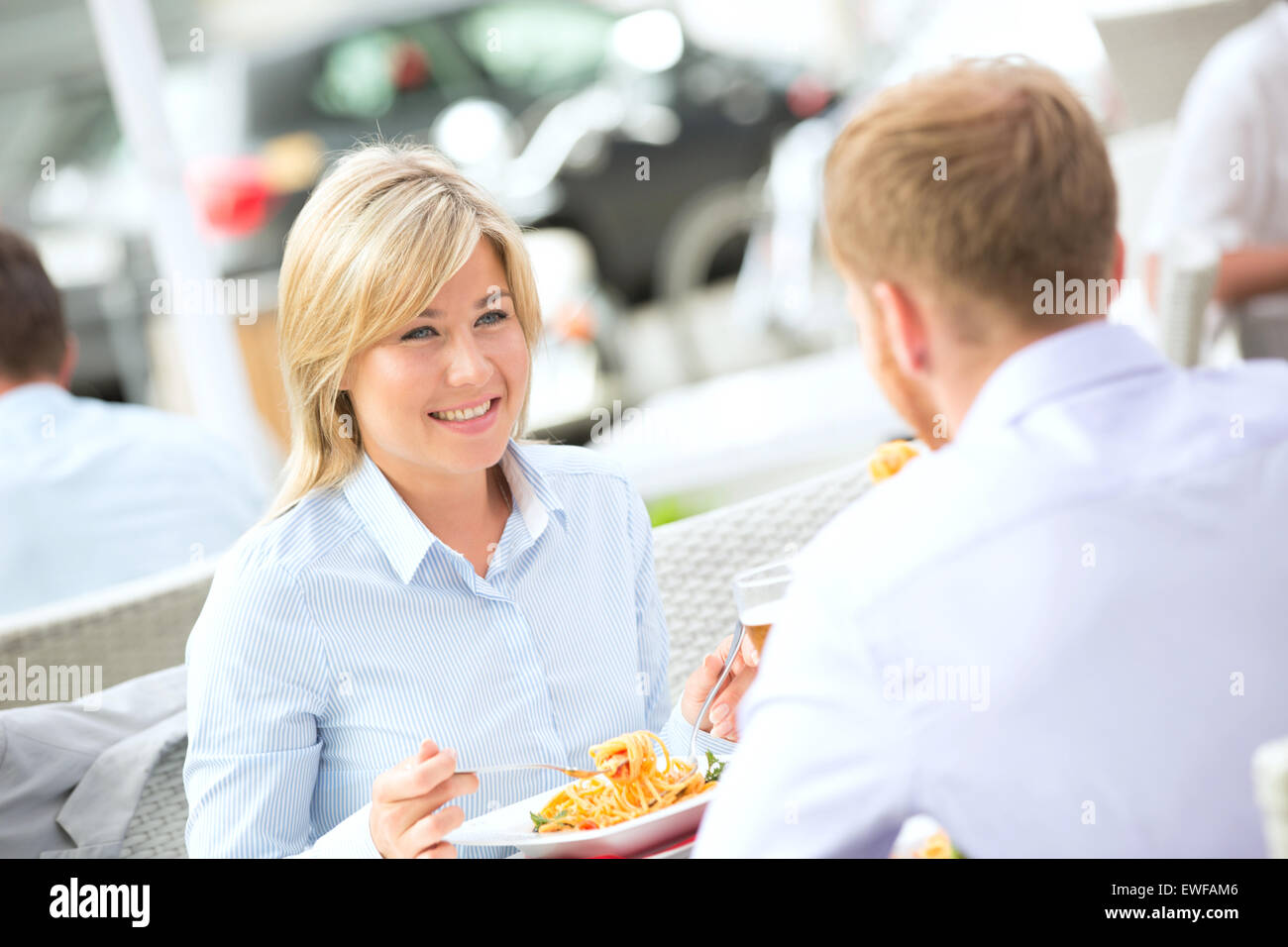 Happy businesswoman having food with male colleague at outdoor restaurant - Stock Image