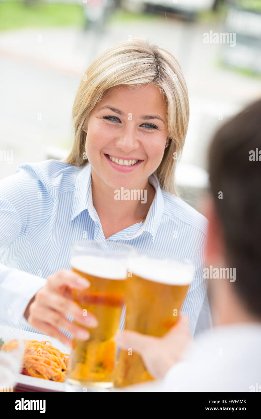 Beautiful businesswoman toasting beer glass with male colleague at restaurant - Stock Image