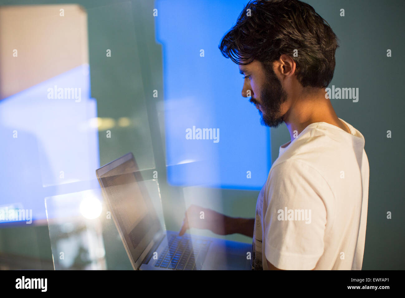 Casual businessman with laptop preparing audio visual presentation - Stock Image