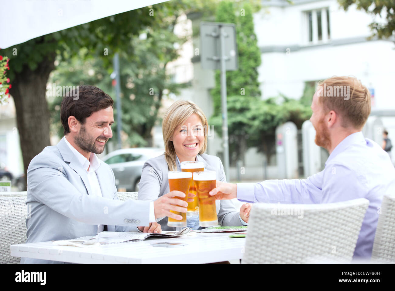 Happy businesspeople toasting beer glasses at outdoor restaurant - Stock Image