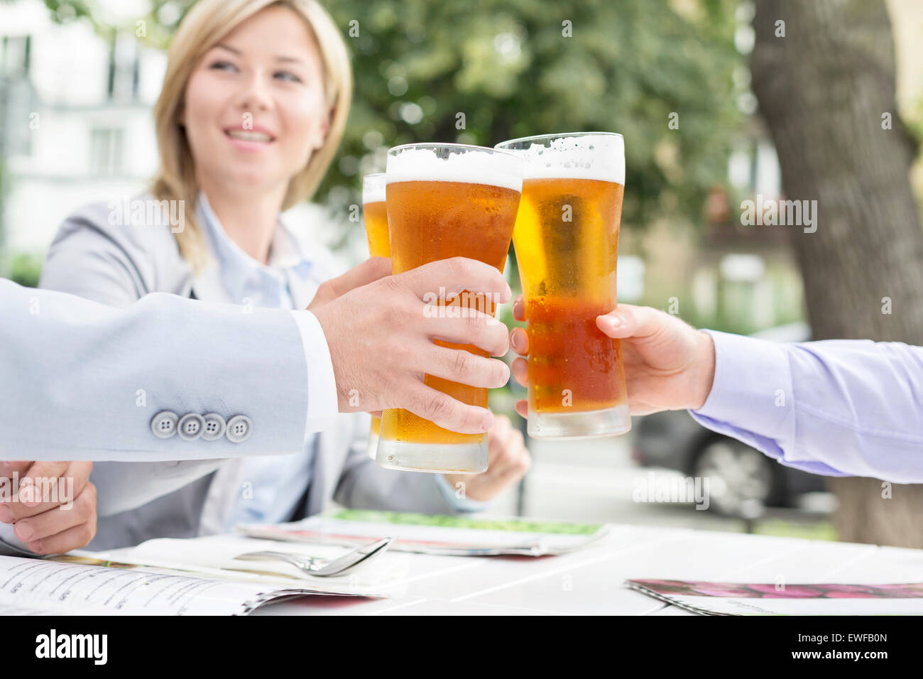 Businesspeople toasting beer glasses at outdoor restaurant - Stock Image