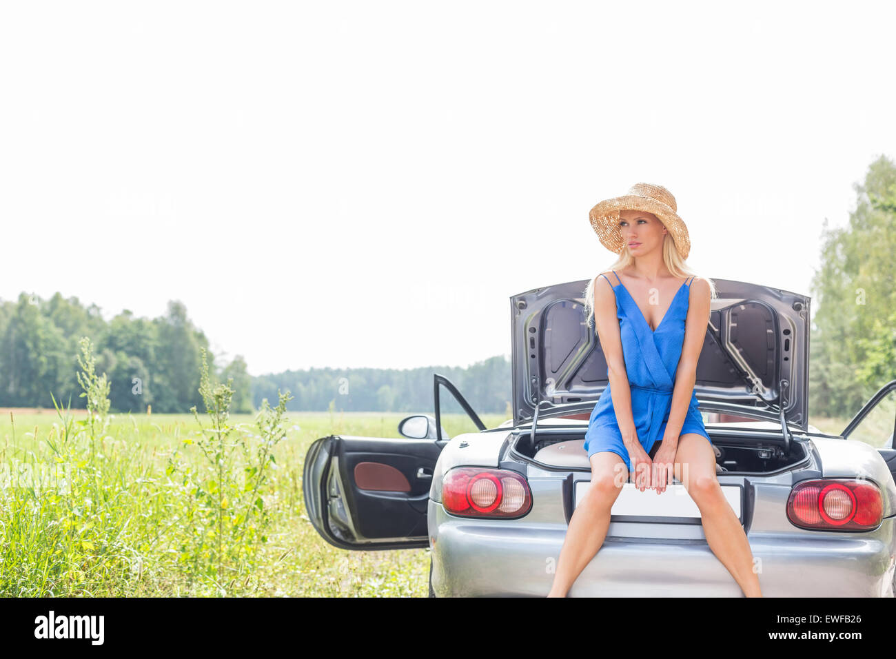 Woman sitting on convertible trunk against clear sky - Stock Image