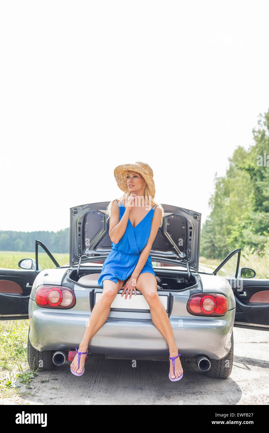Thoughtful woman sitting on convertible trunk against clear sky - Stock Image