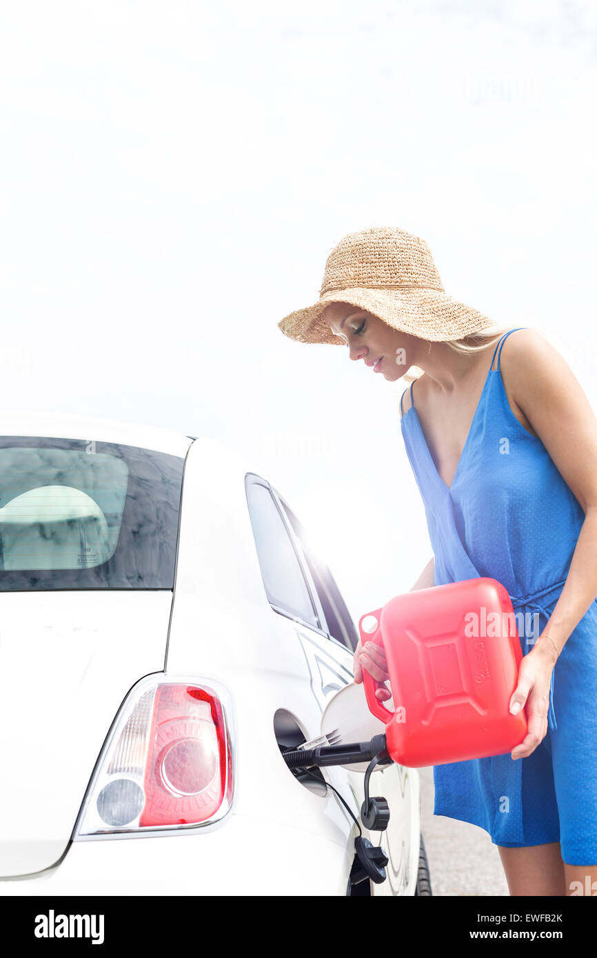 Woman refueling car against clear sky on sunny day - Stock Image