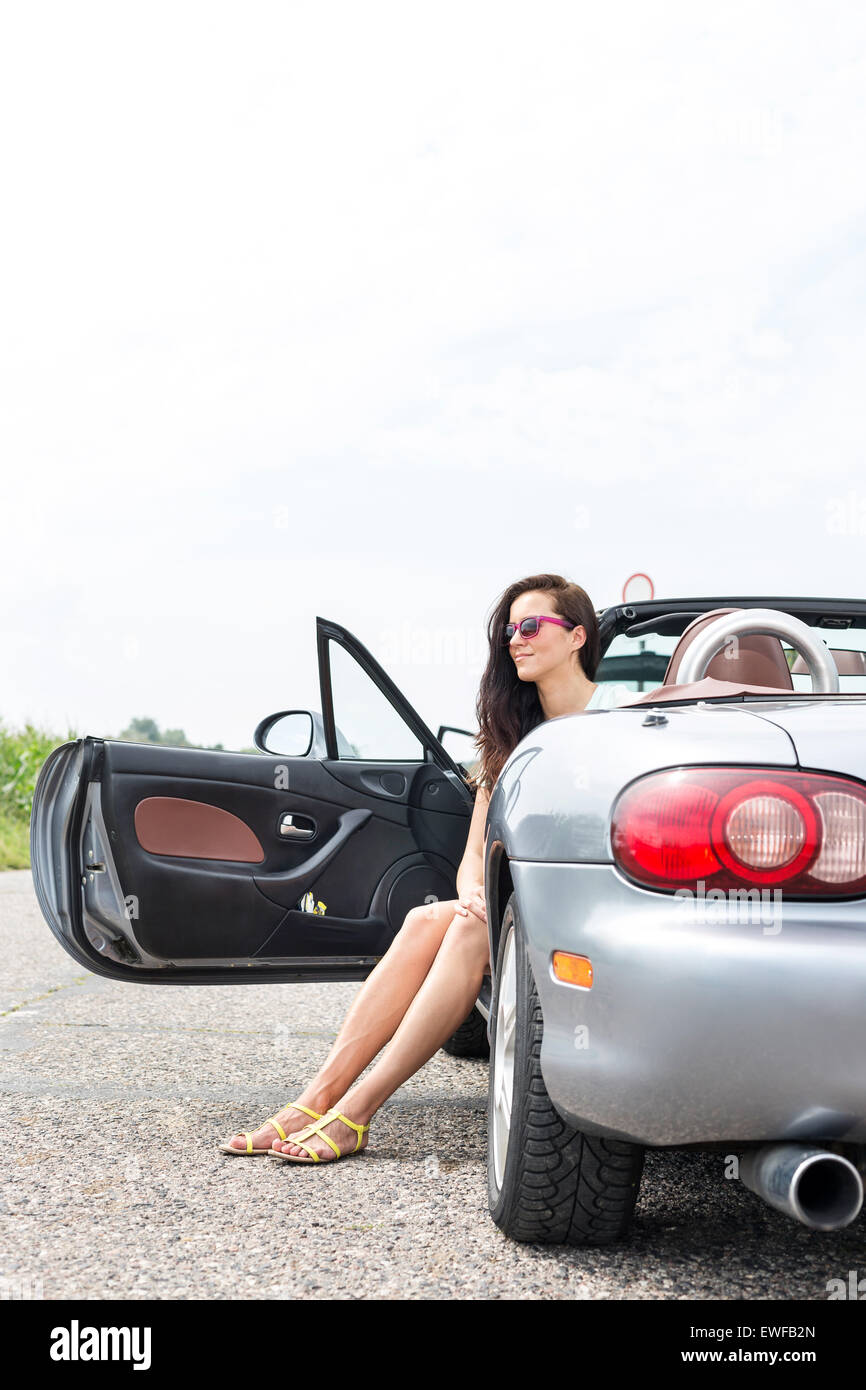 Thoughtful woman sitting in convertible on country road against clear sky - Stock Image