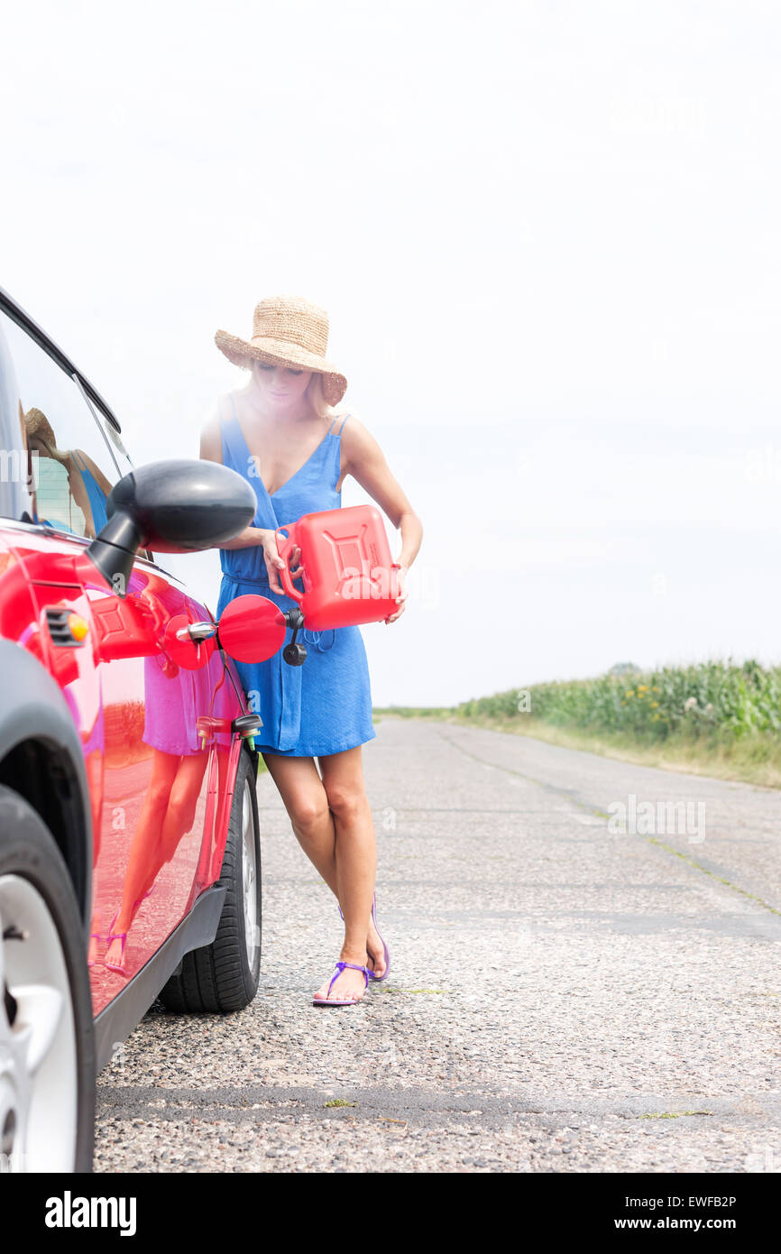 Full-length of woman refueling car on country road against clear sky - Stock Image