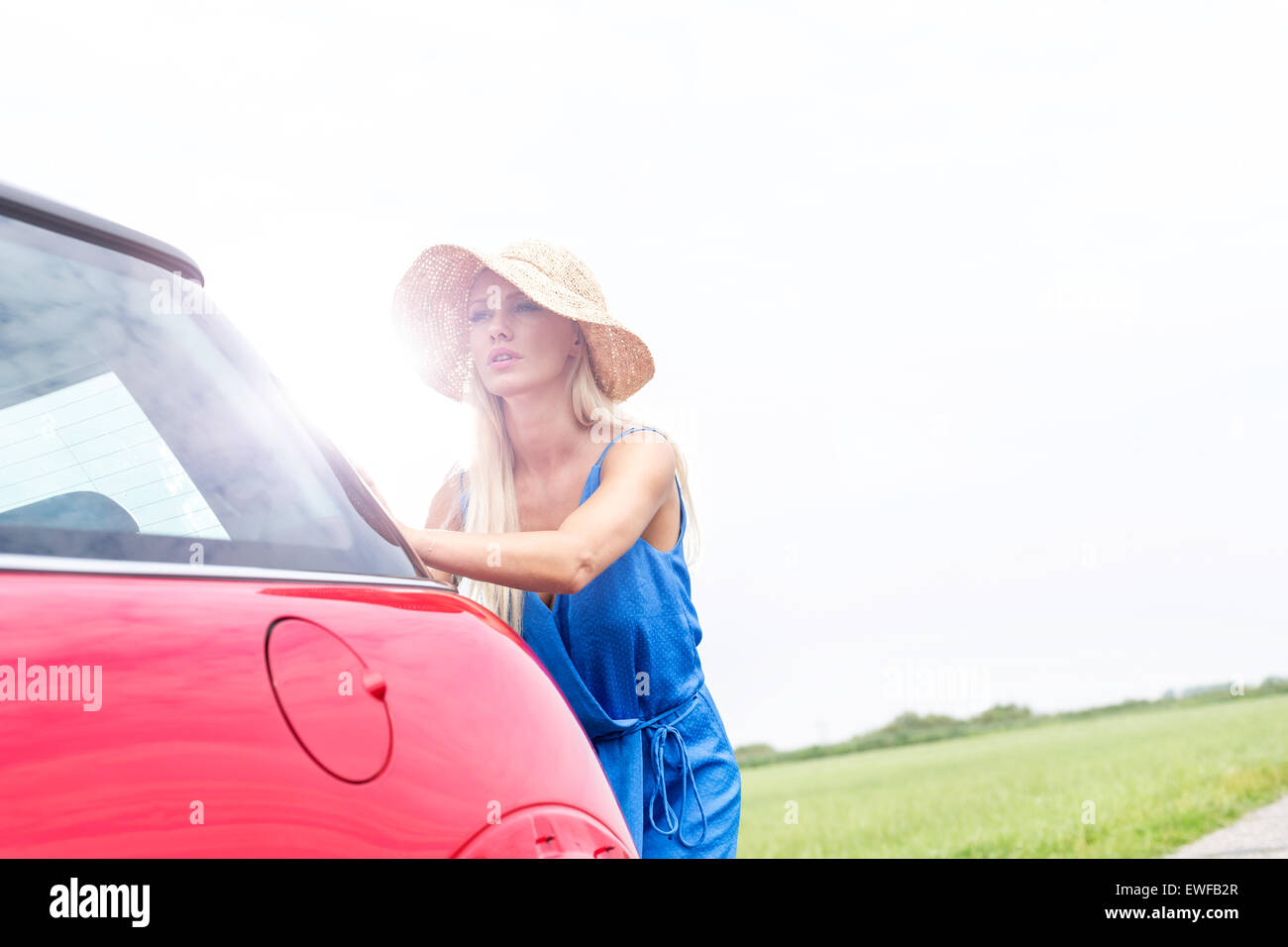 Woman pushing broken down car against clear sky - Stock Image