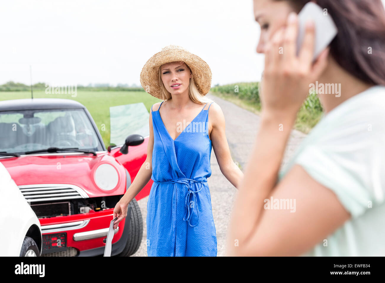 Angry woman looking at female using cell phone by damaged cars on road Stock Photo