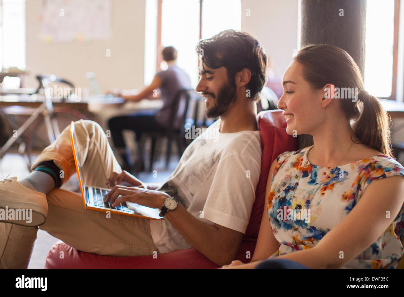 Casual business people using laptop in office - Stock Image