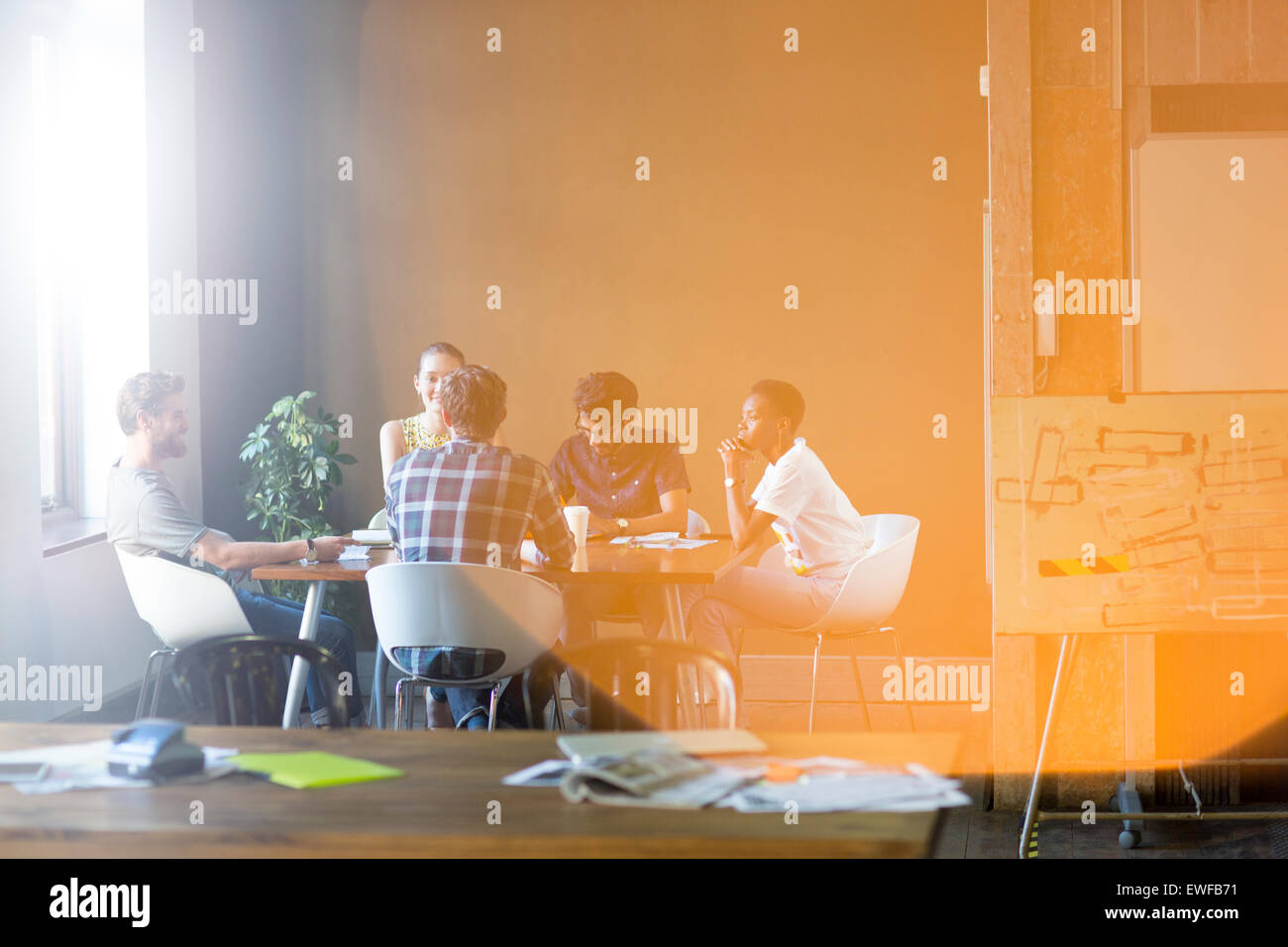 Lens flare over creative business people meeting at office table - Stock Image
