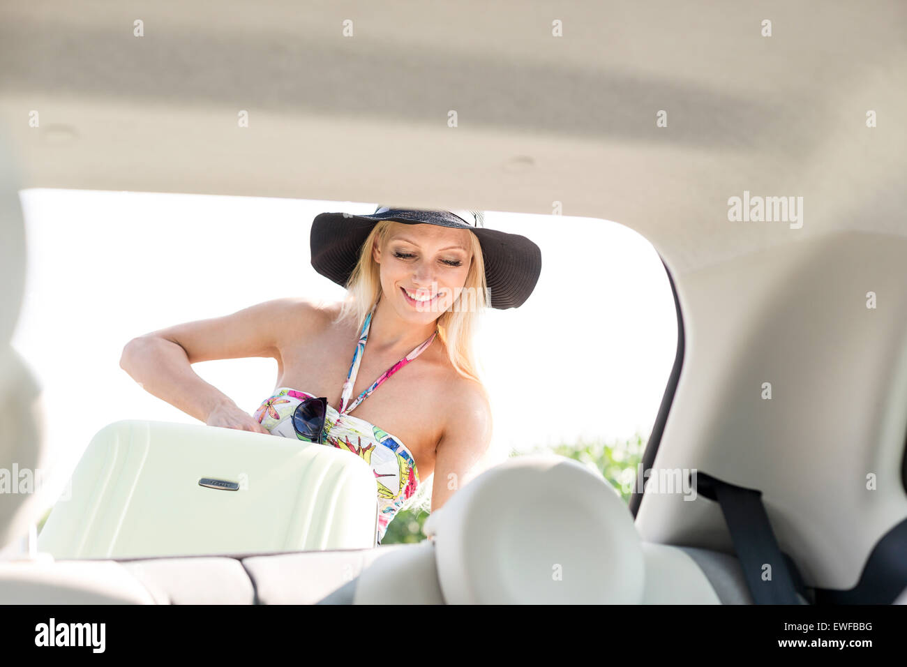 Happy woman loading suitcase in car trunk - Stock Image