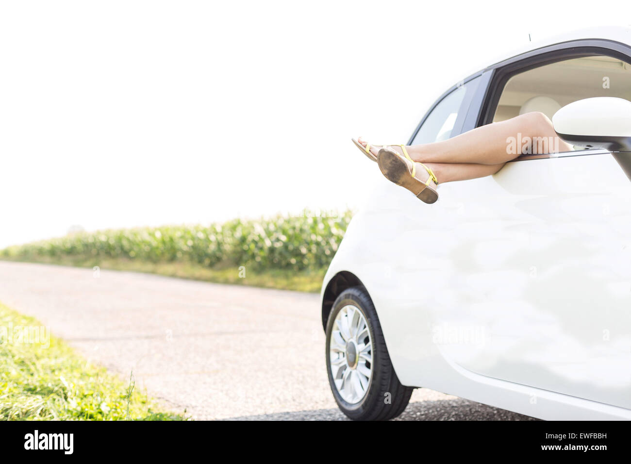 Low section of woman relaxing in car on country road - Stock Image