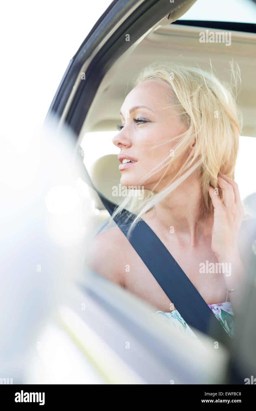 Young woman looking through car window - Stock Image