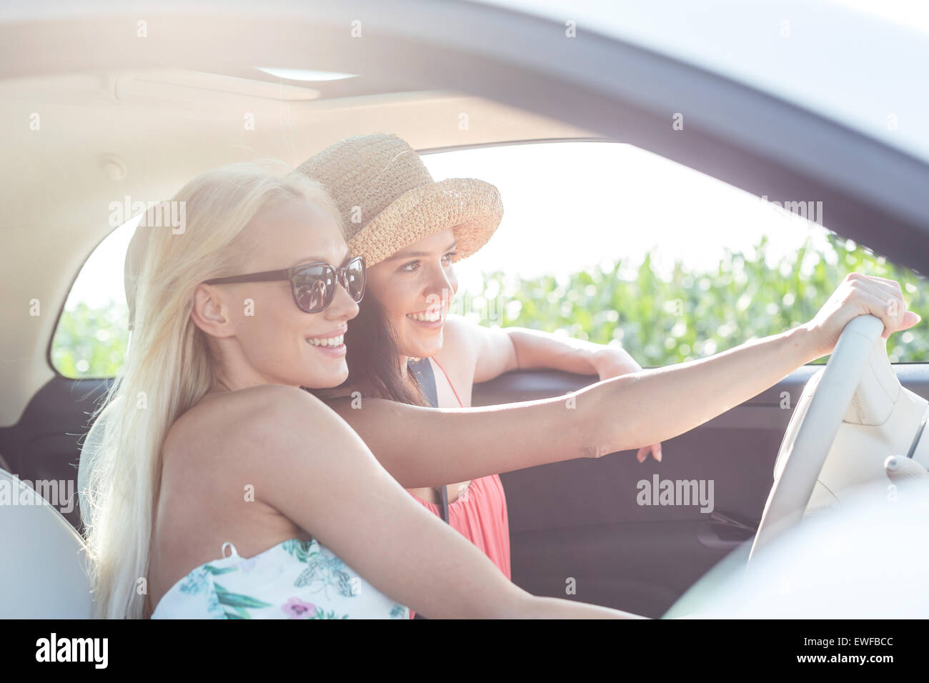 Happy female friends enjoying in car on sunny day - Stock Image