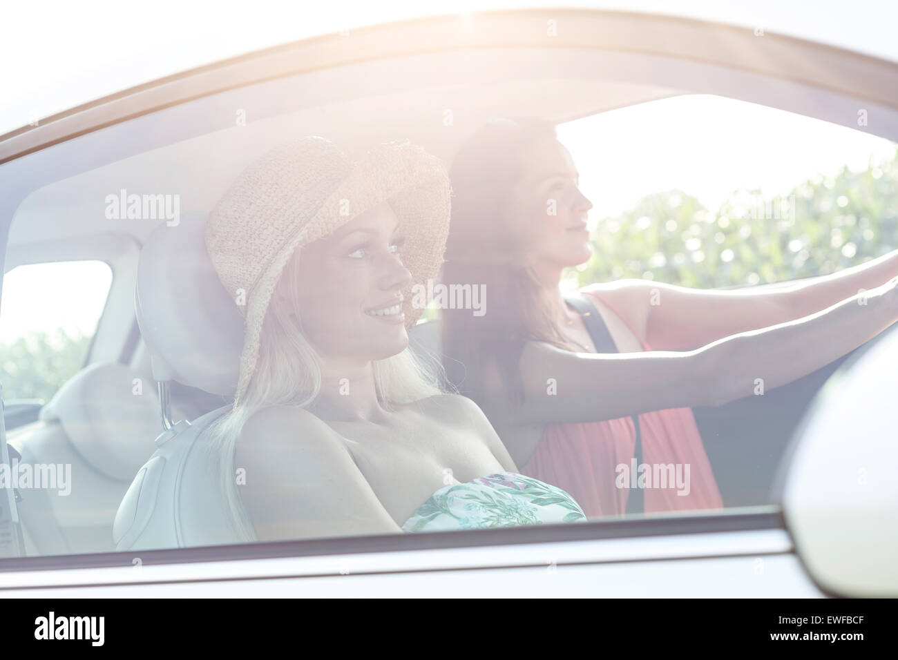 Young female friends in car on sunny day - Stock Image