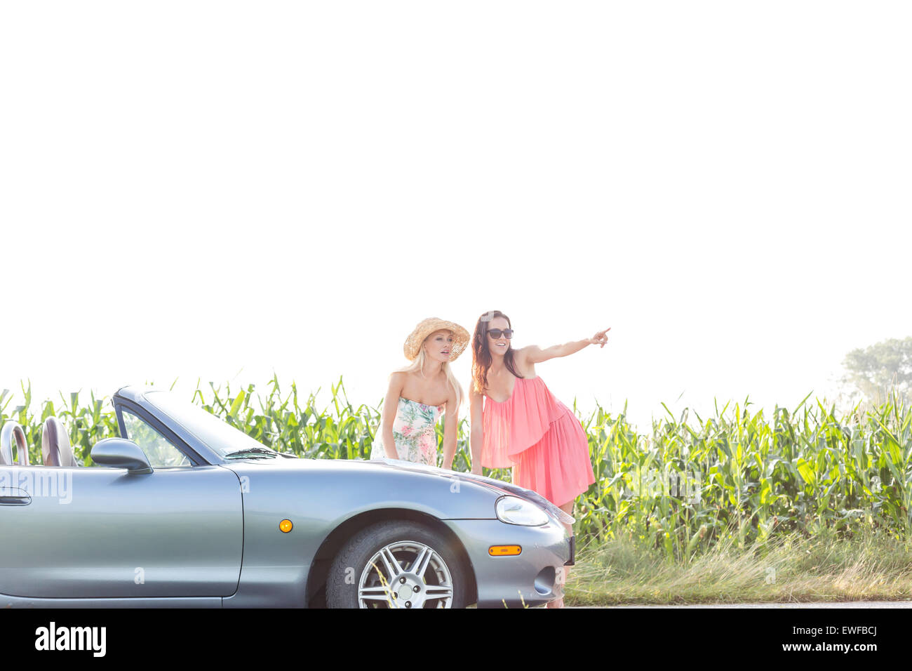 Woman showing something to female friend while standing by convertible - Stock Image