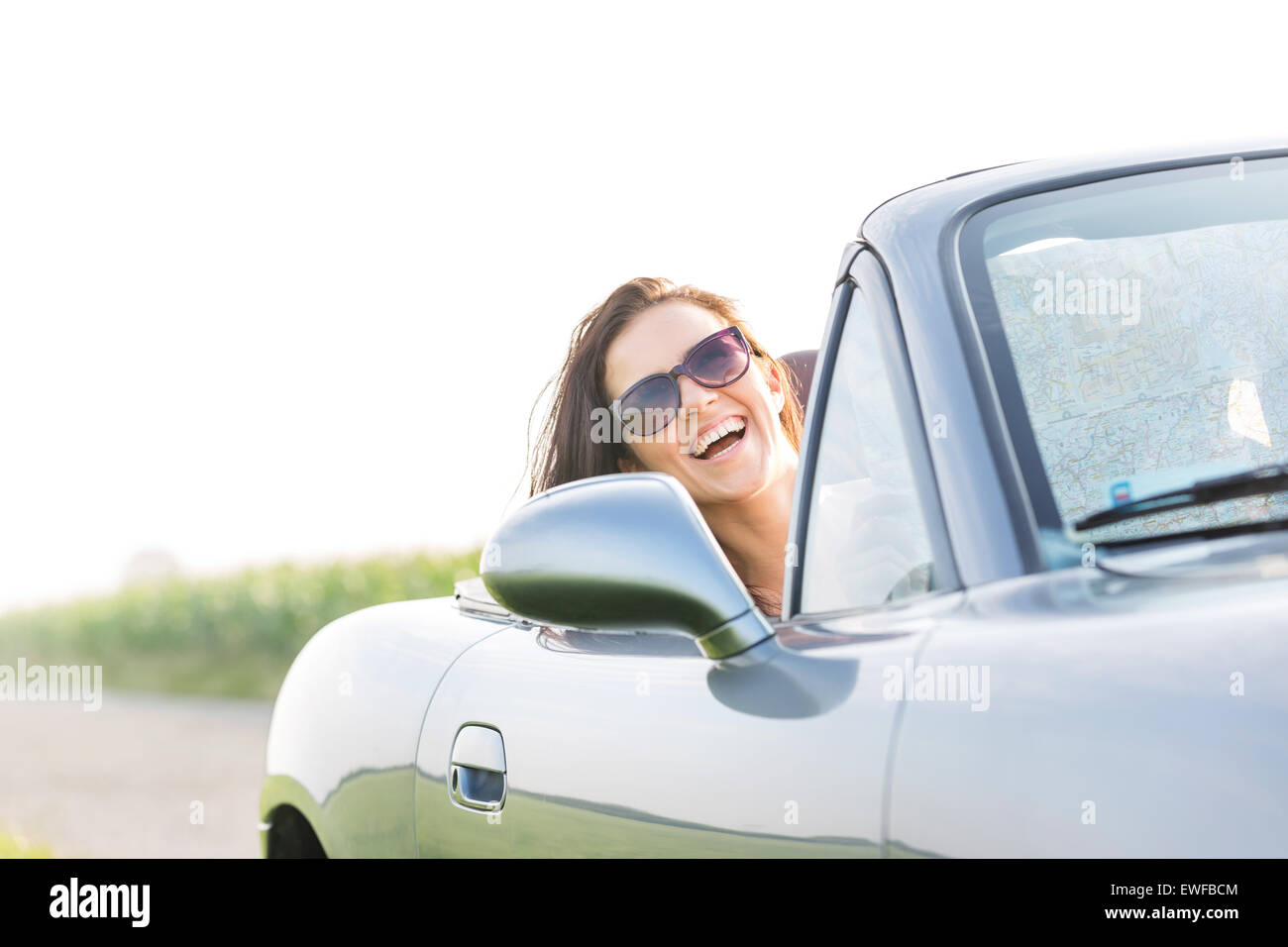 Excited woman enjoying road trip in convertible against clear sky - Stock Image
