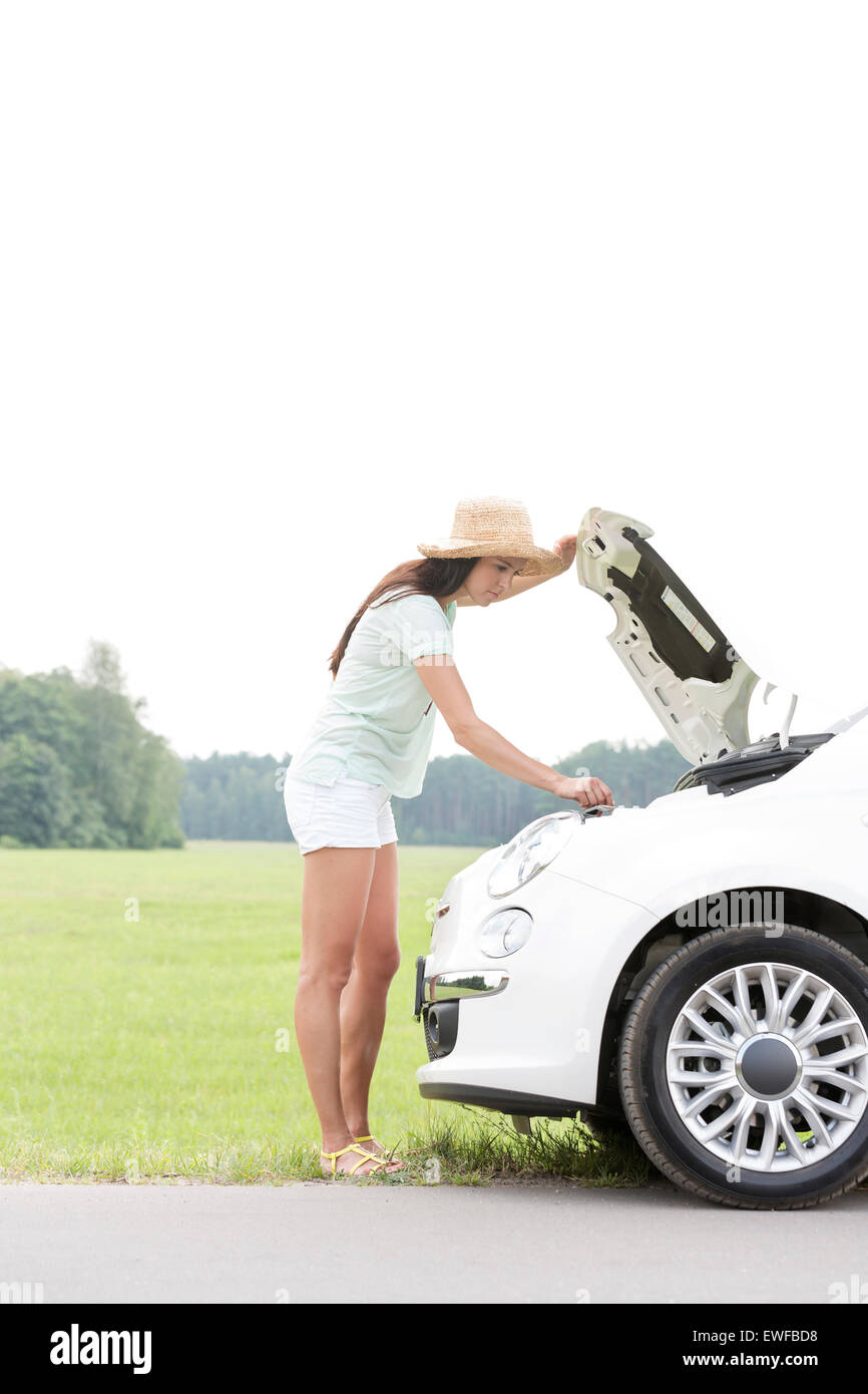 Side view of woman examining broken down car on country road - Stock Image