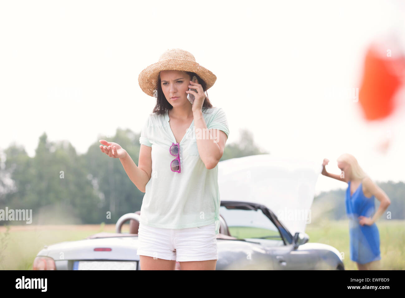 Worried woman using cell phone while friend examining broken down car outdoors - Stock Image