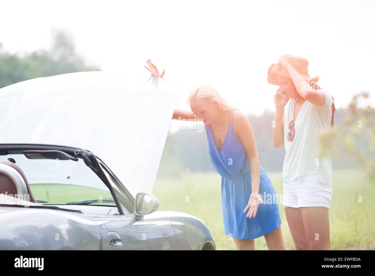 Worried female friends examining broken down car on sunny day - Stock Image