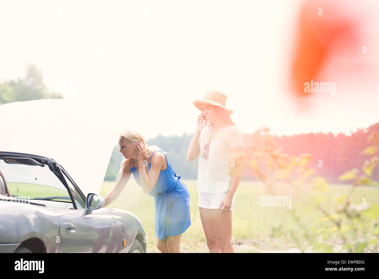 Woman using cell phone while friend examining broken down car - Stock Image