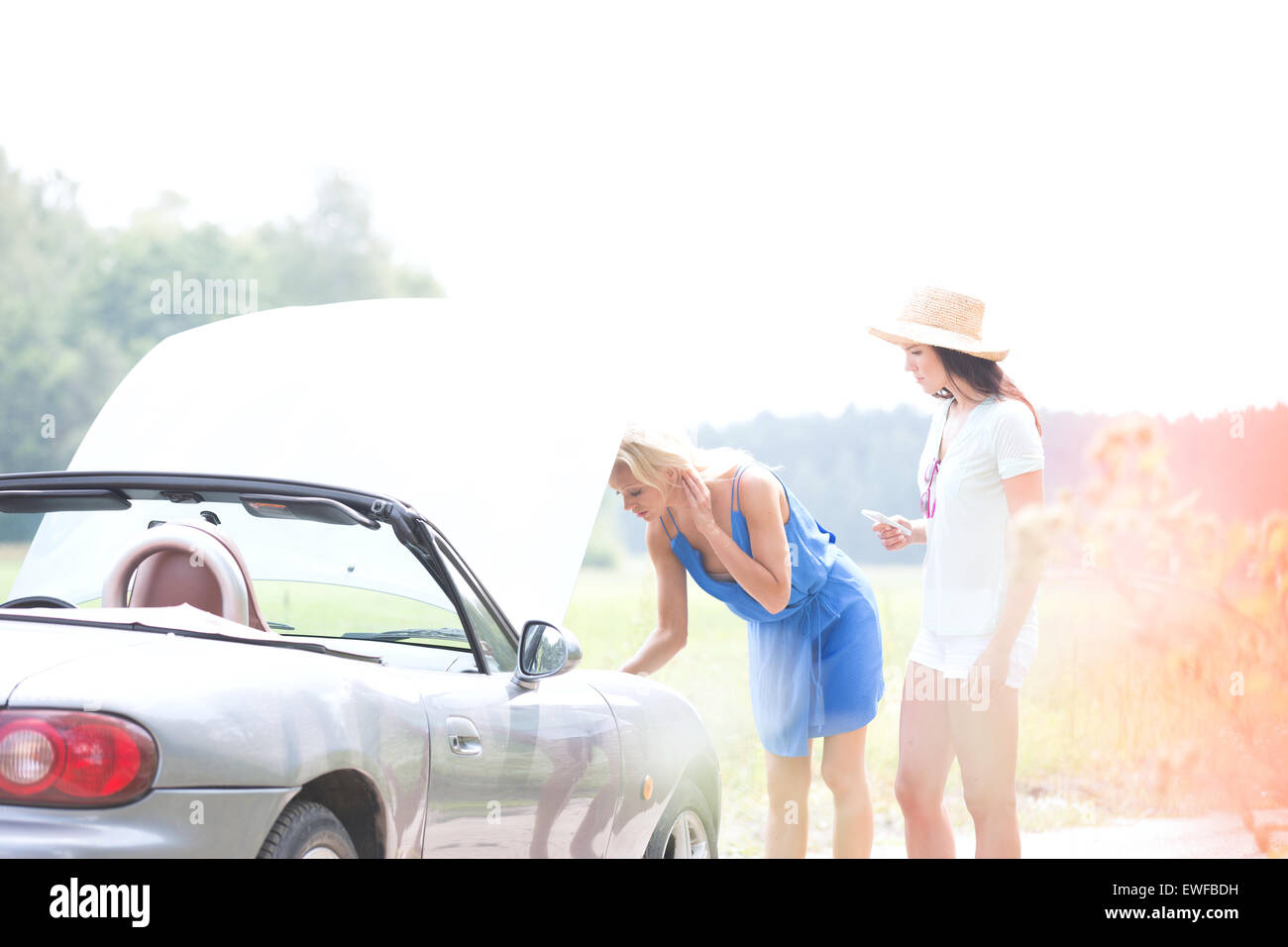 Female friends examining broken down car on country road - Stock Image