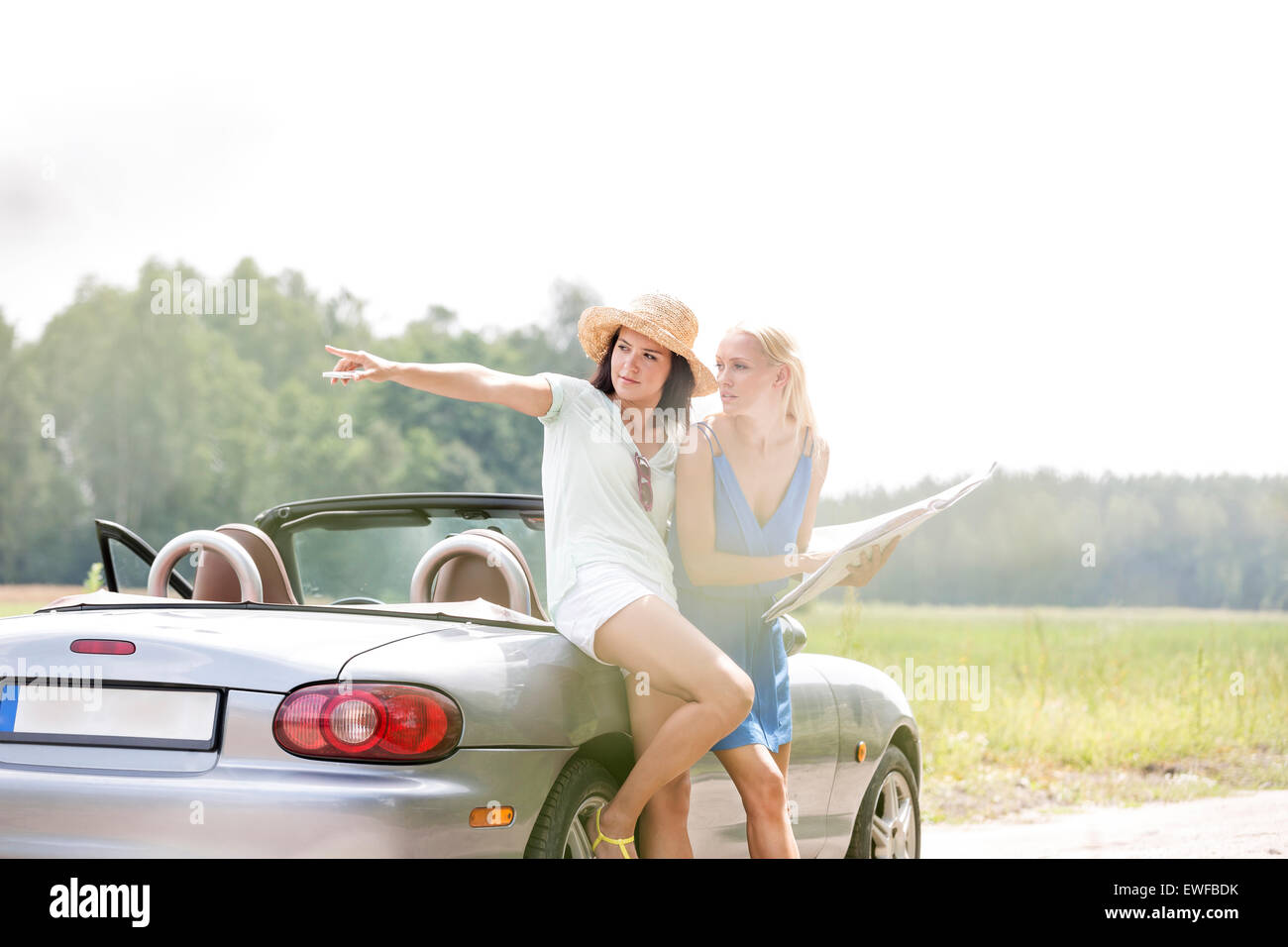 Woman showing something to female friend with map while leaning on convertible - Stock Image