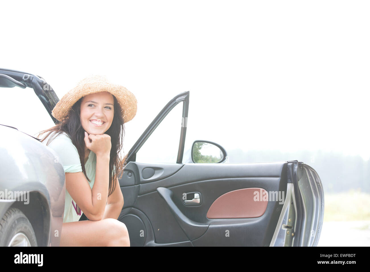 Happy woman sitting in convertible against clear sky - Stock Image