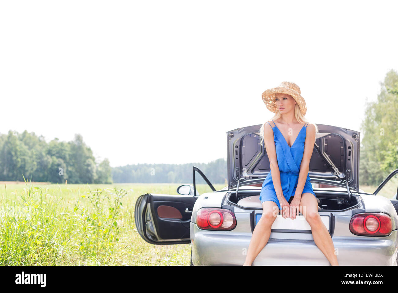 Young woman sitting on convertible trunk against clear sky - Stock Image