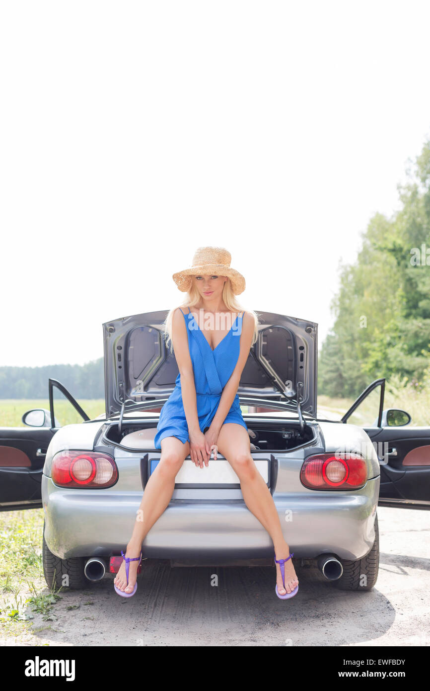 Full length portrait of woman sitting on convertible trunk against clear sky - Stock Image