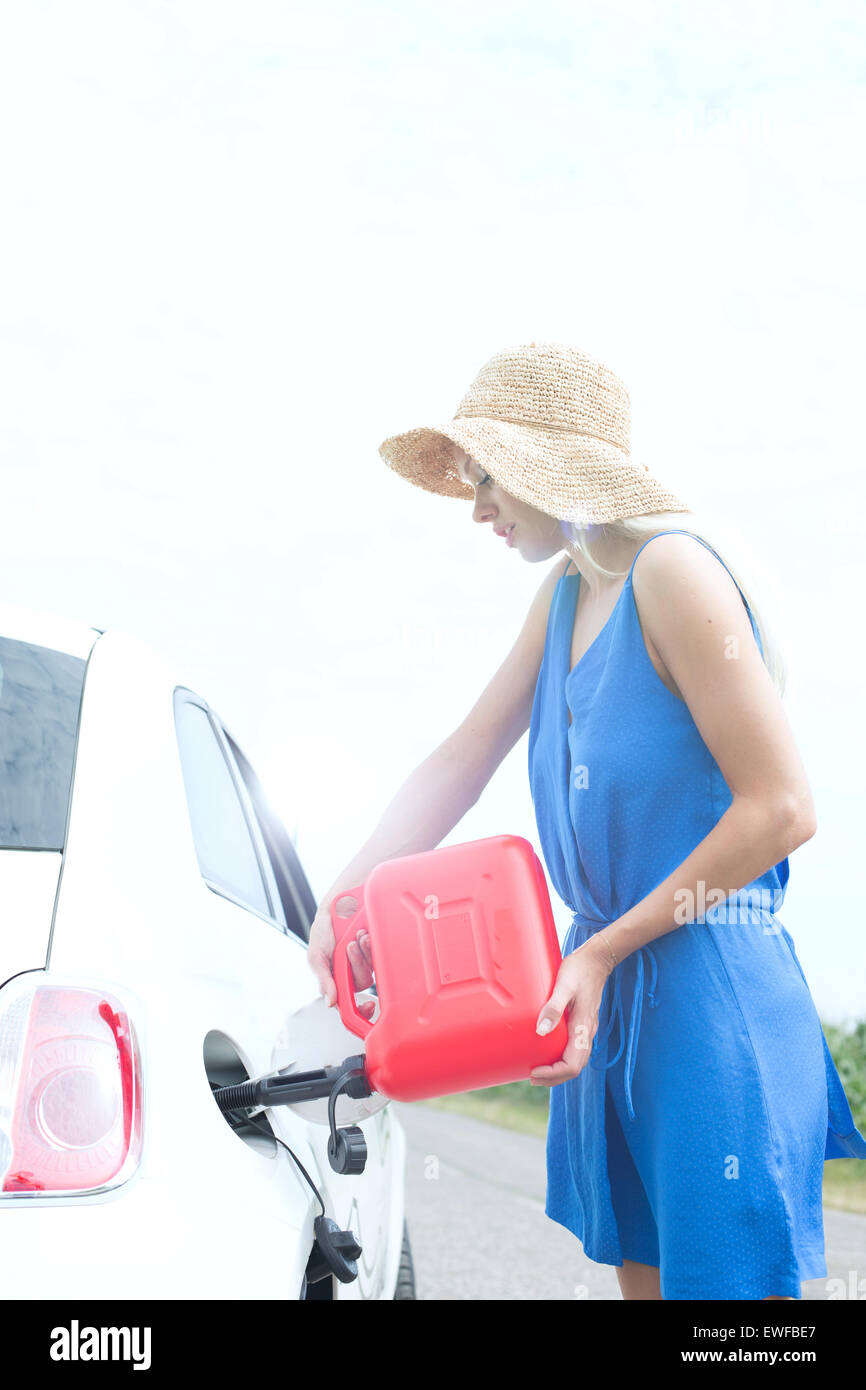 Side view of woman refueling car on country road - Stock Image
