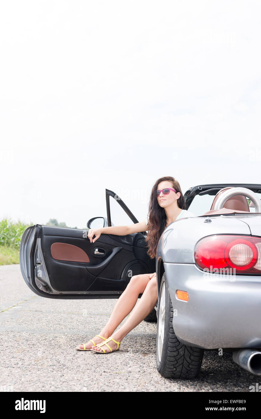 Young woman sitting in convertible on country road against clear sky - Stock Image