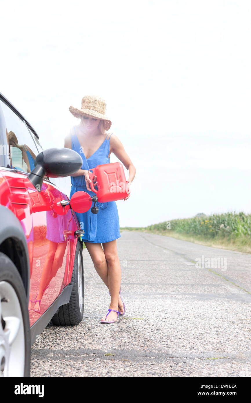 Full length of young woman refueling car on country road - Stock Image