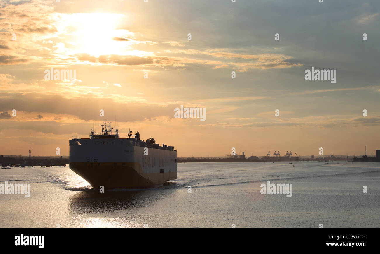 A car transporter ship pictured leaving Southampton docks at sunset - Stock Image