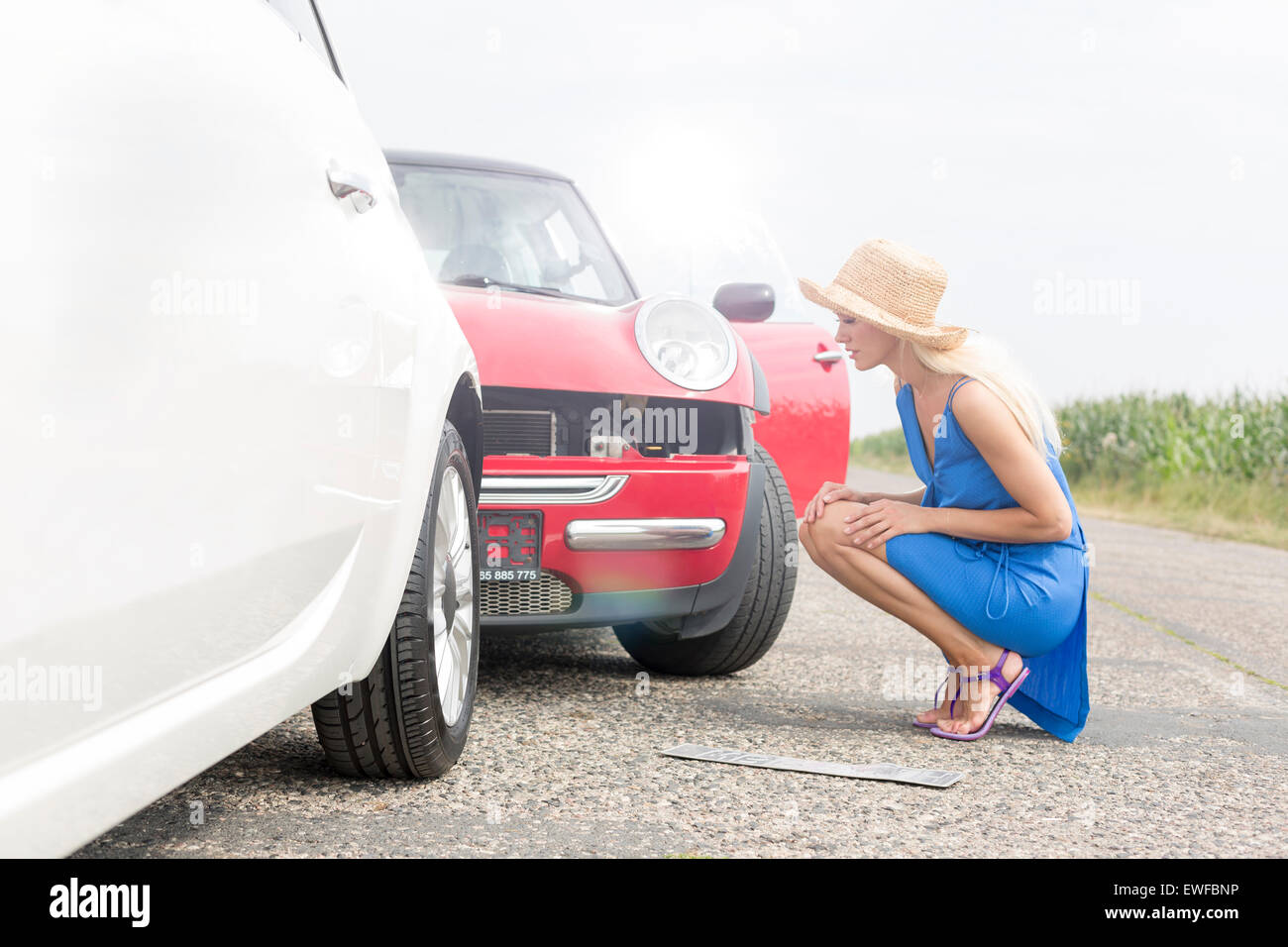 Full-length side view of tensed woman looking at damaged cars on road - Stock Image