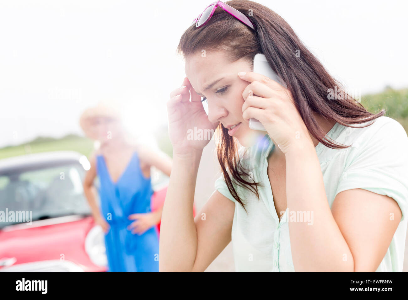 Worried woman using mobile phone while friend standing by broken down car on sunny day - Stock Image