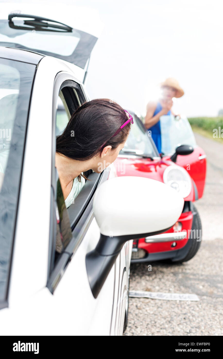 Woman looking at female crashing car on road - Stock Image