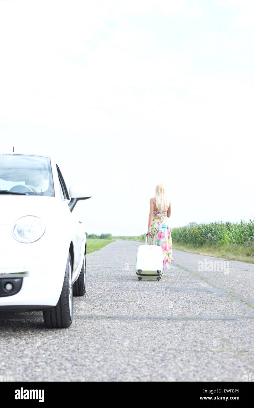 Rear view of woman with luggage leaving broken down car on country road - Stock Image