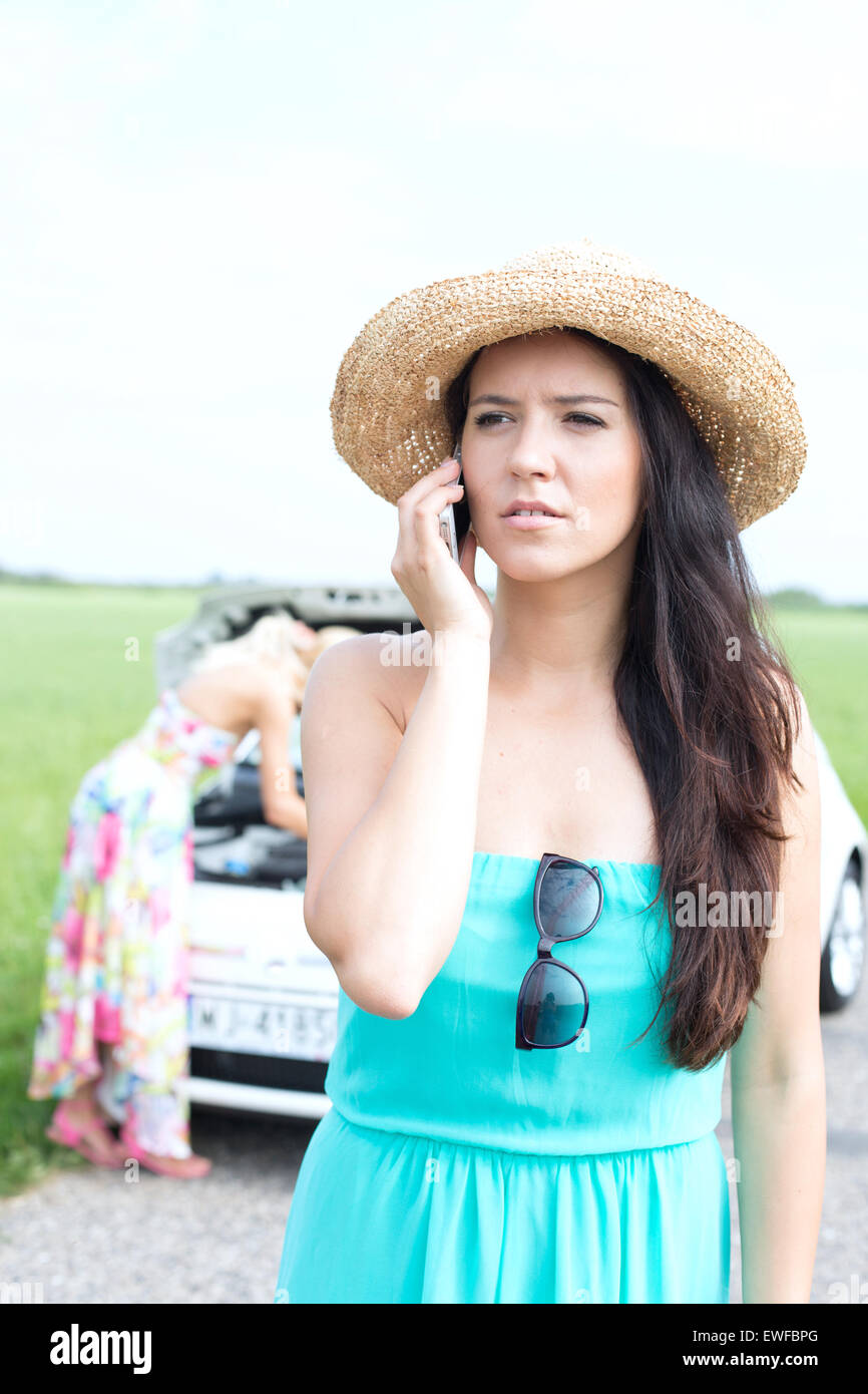 Worried woman using mobile phone while friend examining broken down car at countryside - Stock Image