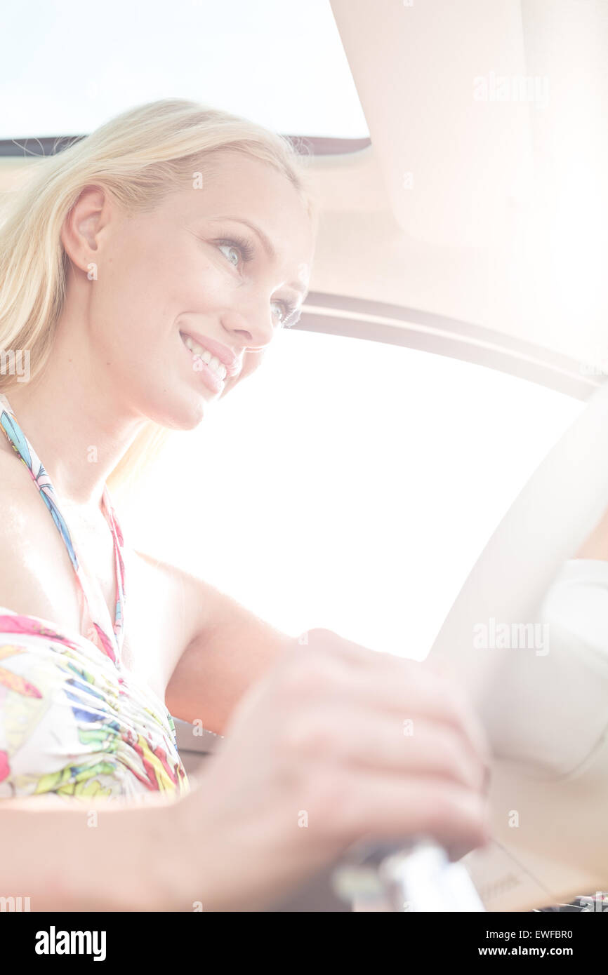 Low angle view of smiling woman driving car - Stock Image
