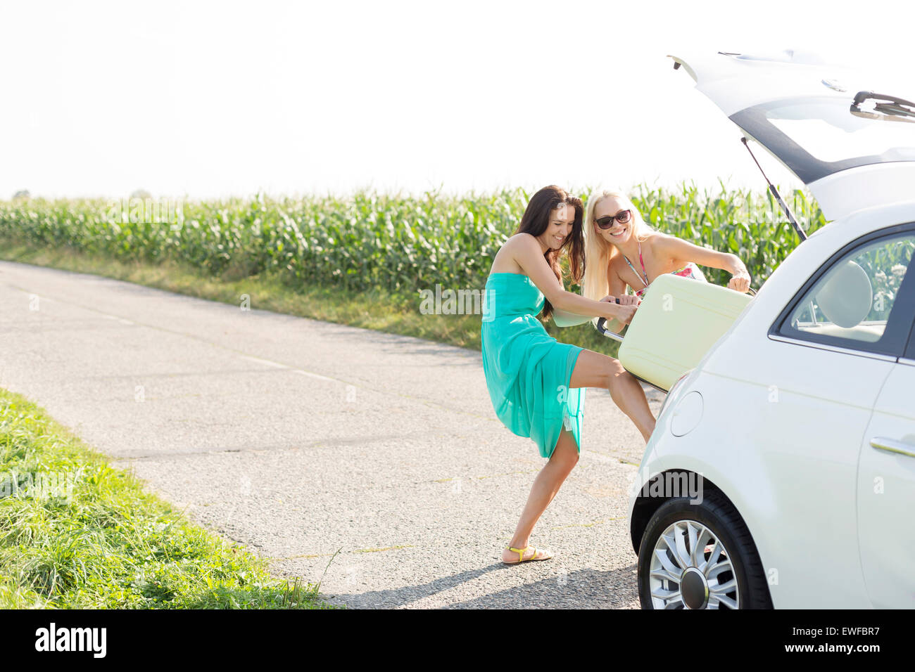 Happy female friends pushing luggage in car trunk against clear sky - Stock Image