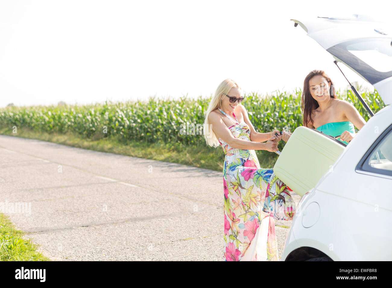 Happy women loading luggage in car trunk against clear sky - Stock Image