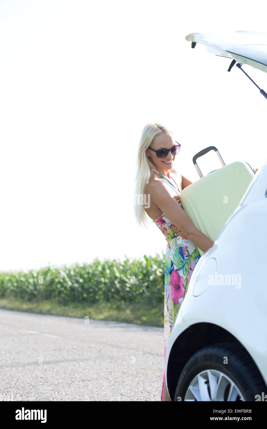 Happy woman loading suitcase in car trunk against clear sky - Stock Image
